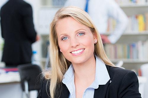 Tarifwechsel Private Krankenversicherung Deutscher Ring - Wechsel PKV - Lächelnde Frau im Büro