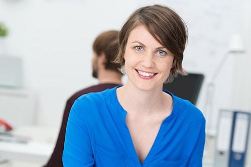 Tarifwechsel Private Krankenversicherung HUK-Coburg - Wechsel PKV - Lächelnde Beraterin am Arbeitsplatz