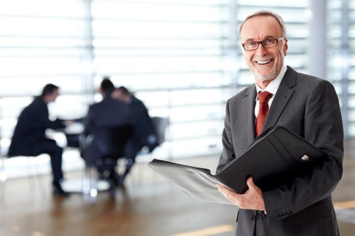 Tarifwechsel Private Krankenversicherung Inter - Wechsel PKV - Lächelnder Geschäftsmann hällt Unterlagen in der Hand